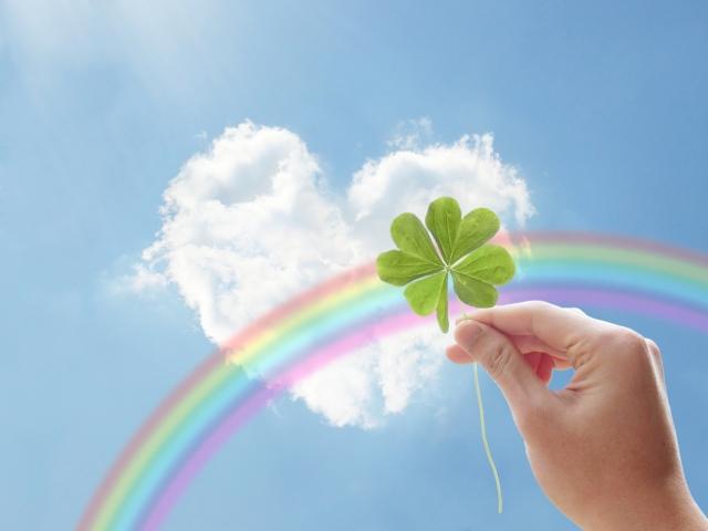 ハート型の雲と青空と虹四つ葉のクローバーを持つ手画像